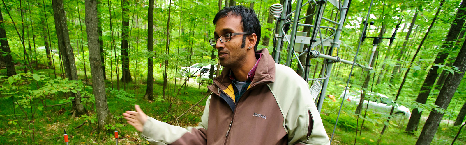 Ankur Desai stands in front of a 27-meter-tall flux tower in a wooded area near Minocqua, Wisconsin.